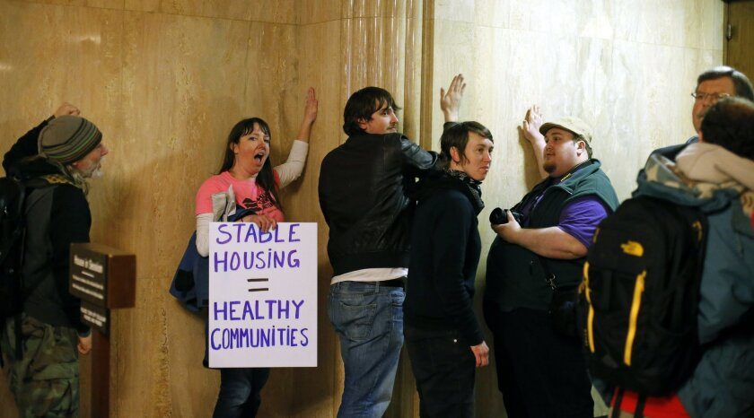 Protesters pound on the walls outside of the House Chamber in the Capitol Building, in Salem , Ore., on Thursday, Feb. 18, 2016. The group were protesting for a higher minimum wage, local control of rent control laws, and an end to Oregon Department of Transportation sweeps of homeless camps. (AP P