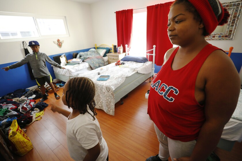 Anna Gray in her room that she shares with her children, Harold, 9, and Patrick, 5, at a recently opened temporary shelter.