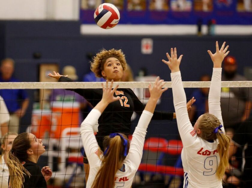 Huntington Beach High's Xolani Hodel (12), seen battling at the net against Los Alamitos during a Surf League match on Sept. 19, has verbally committed to play beach volleyball at Stanford.