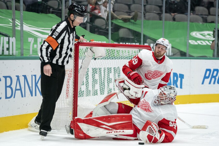 FILE - In this Thursday, Jan. 28, 2021 file photo, Detroit Red Wings goaltender Jonathan Bernier (45) and right wing Anthony Mantha (39) look to referee Chris Lee after the net broke free from its moorings on a goal by Dallas Stars' Andrew Cogliano during the second period of an NHL hockey game in Dallas. NHL referees and linesmen working multiple consecutive games between the same teams has allowed them to build up more of a rapport with players even amid pandemic restrictions. Officials are seeing each other less before and after games but getting to know players better on and off the ice in part because they're in the same cities more often. (AP Photo/Jeffrey McWhorter, File)