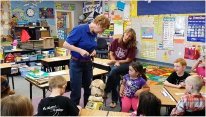 The Julian Elementary School students also received a visit from Jenga, a Canine Companion and official Del Mar Rotarian, along with her owner Donna Fipps and other Rotary members. Pictured here with teacher Tere Tangeman.