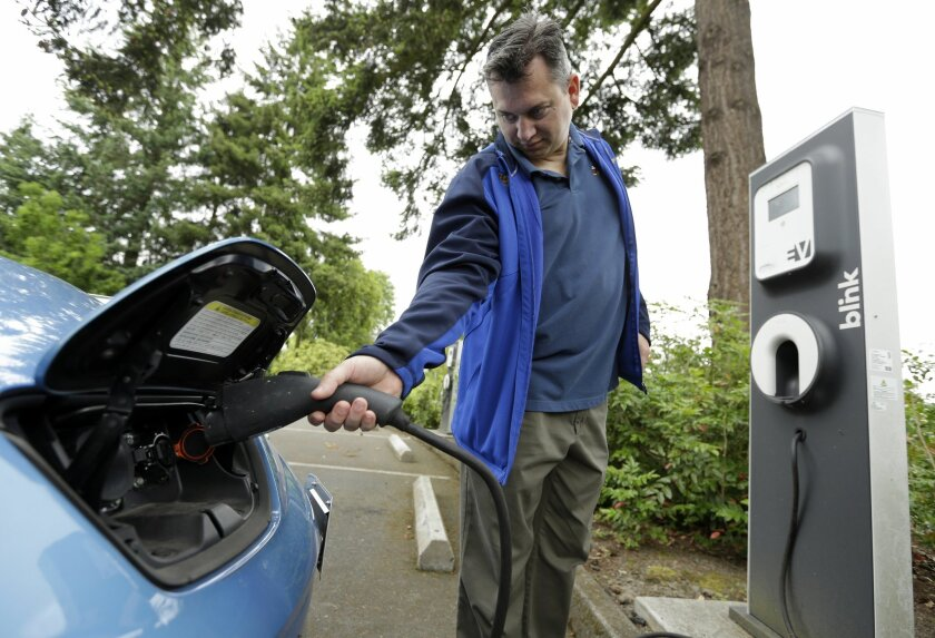 Patrick Conner' shows how to plug his Nissan Leaf electric car at a charging station at the public library in Hillsboro, Ore., Tuesday, May 19, 2015.    Fuel-efficient, hybrid and electric cars are a boon for the environment, but their growing popularity means shrinking fuel tax revenues for state