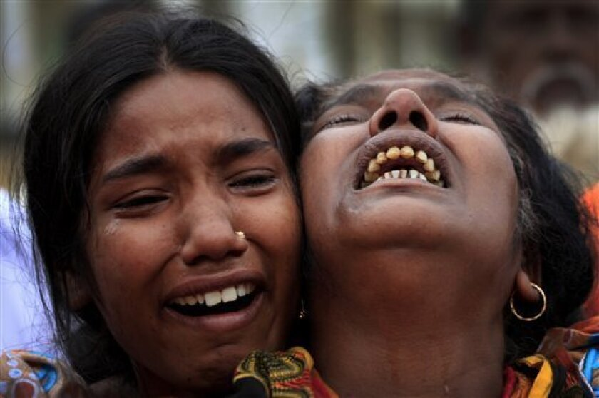 A woman is comforted as she grieves after identifying the body of her daughter, a victim of the garment factory collapse, Sunday, May 5, 2013 in Savar, near Dhaka, Bangladesh. The death toll from the collapse of a shoddily built garment-factory building in Bangladesh continued its horrifying climb, reaching 580 on Sunday with little sign of what the final number will be. The disaster is likely the worst garment-factory accident ever, and there have been few industrial accidents of any kind with