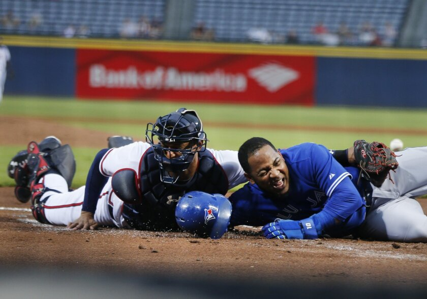 Toronto Blue Jays' Edwin Encarnacion (10) scores on a Russell Martin double as the ball gets away from Atlanta Braves catcher Christian Bethancourt (27) in the first inning of a baseball game Wednesday, Sept. 16, 2015, in Atlanta. (AP Photo/John Bazemore)