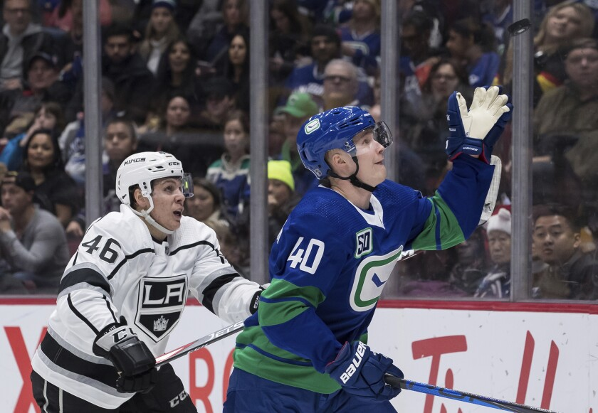 The Canucks' Elias Pettersson, right, reaches for the puck in front of the Kings' Blake Lizotte during the third period Saturday.