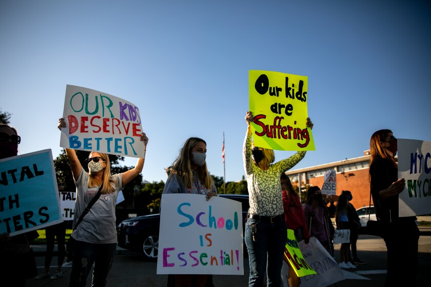 Protesters hold signs at San Diego Unified headquarters in October calling for schools to reopen.