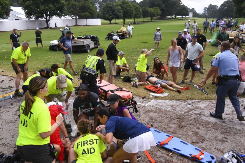 Spectators are tended to on the golf course after a lightning strike.