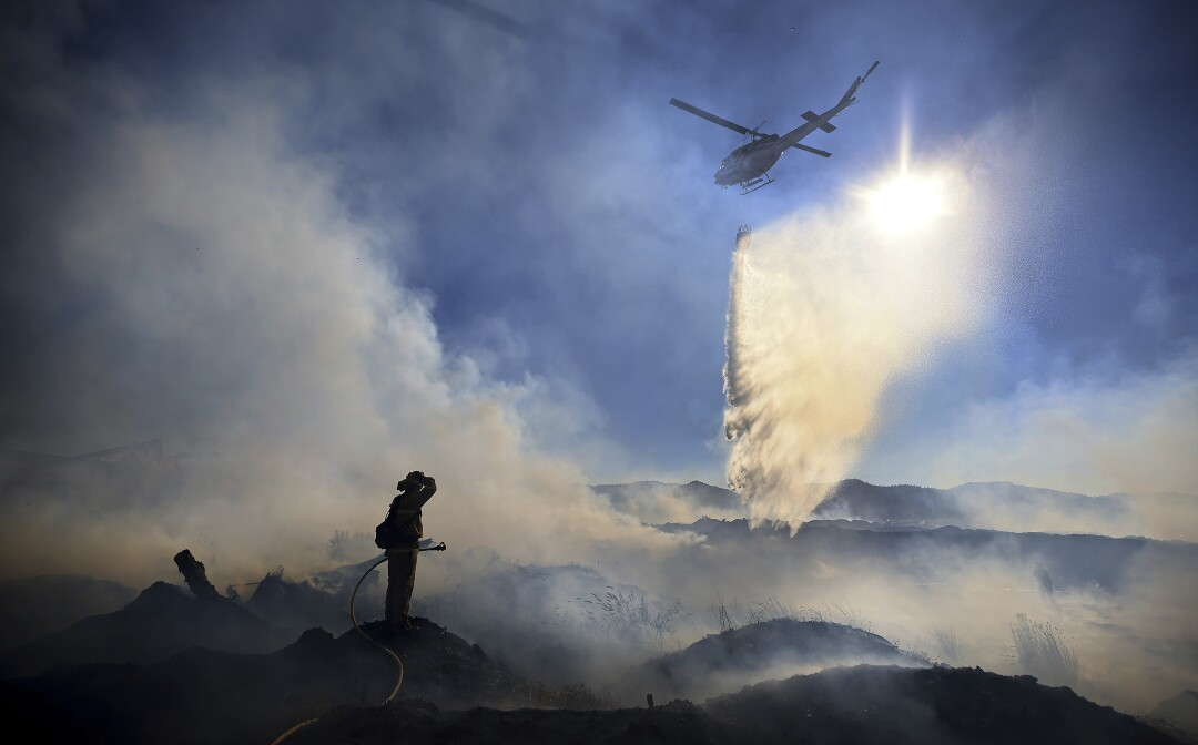 A firefighter pauses on a hill as a helicopter flies past