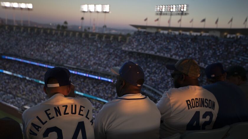LOS ANGELES, CALIF. -- FRIDAY, OCTOBER 26, 2018: The sunset lights up the jerseys of Dodgers fans wa