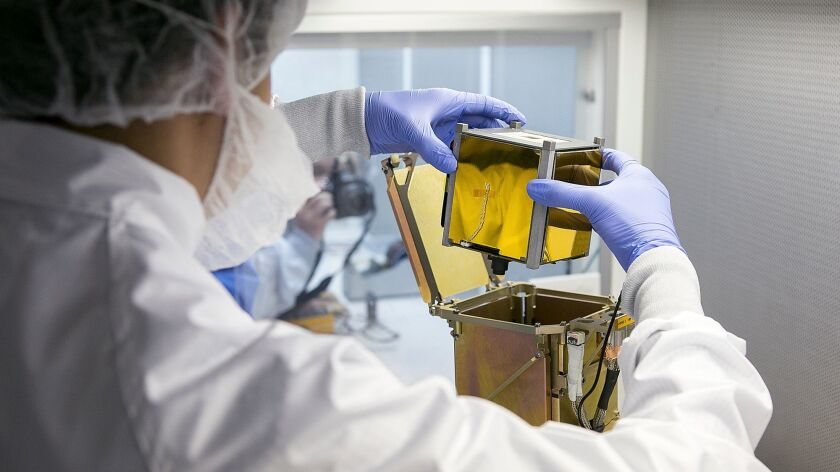 Vidur Kaushish, a mission manager at Tyvak Nano-Satellite Systems, Inc., places a CubeSat, or nano-s
