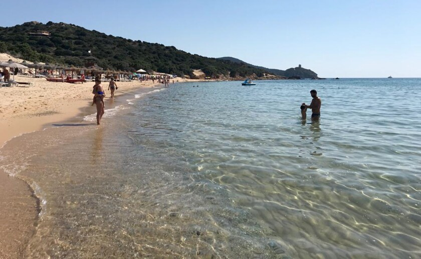personas disfrutando de la arena y el agua en la playa Chia, en la isla italiana de Sardinia, Italia