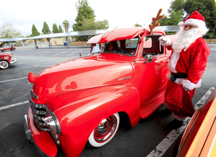 Dressed as Santa, Roberto Montes from the San Diego County Probation stands next to a red 1950 Chevrolet truck fitted with red nose and reindeer antlers. Santa and the lowrider were among the lowrider owners taking part at the annual Toy Drive and Car Show held at Southwestern College in Chula Vista on Sunday, December 8, 2019.