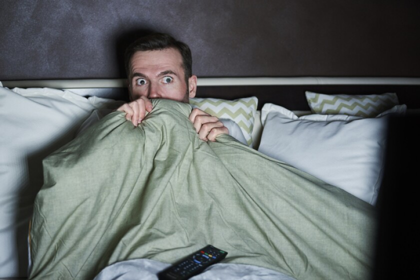 Scared man watching horror movies at night