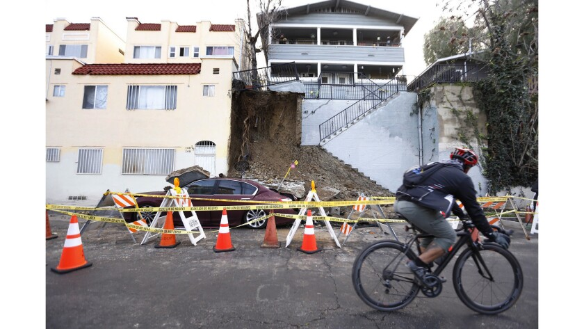 A car is partially buried by soil and concrete after rain collapsed a staircase in Echo Park.