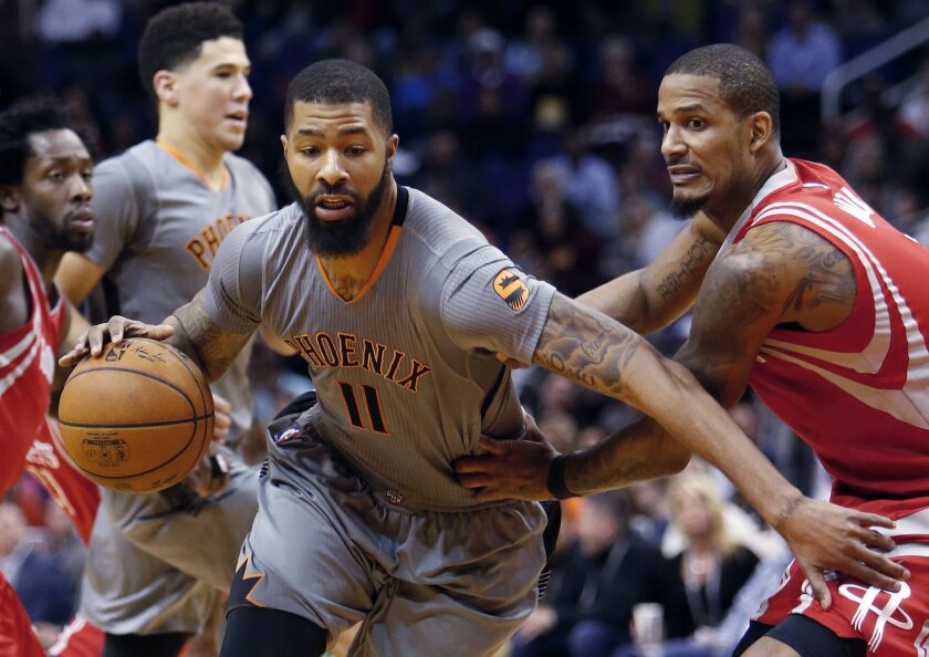 FILE - In this Thursday, Feb. 4, 2016 file photo, Phoenix Suns forward Markieff Morris (11) drives past Houston Rockets forward Trevor Ariza during the fourth quarter of an NBA basketball game in Phoenix. A person familiar with the deal says forward Markieff Morris has been traded by the free-falling Phoenix Suns to the Washington Wizards, a team hoping to boost its chances of making the playoffs, Thursday, Feb. 18, 2016. (AP Photo/Rick Scuteri, File)