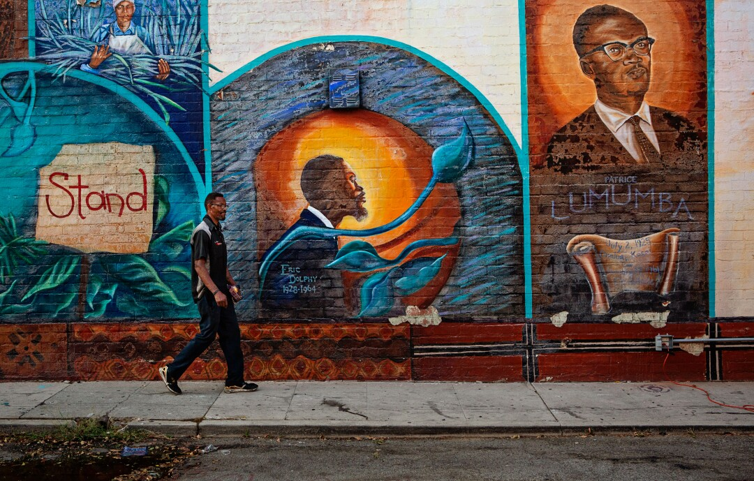 A man walks by a mural Leimert Park.