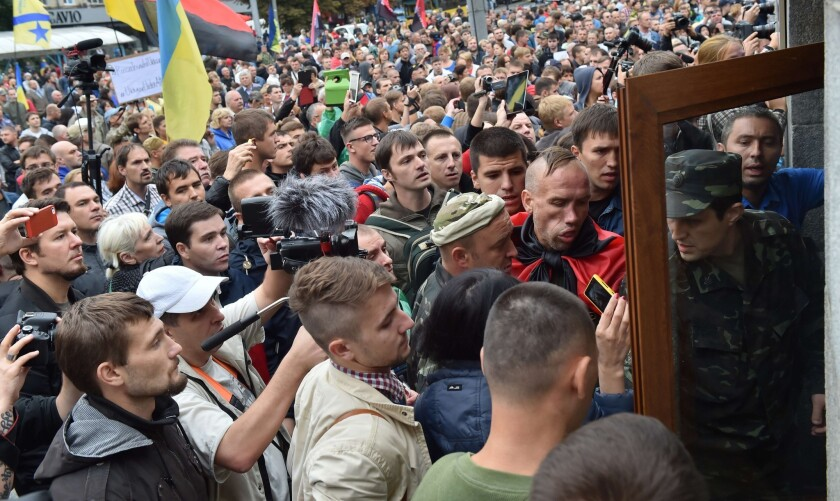 Protesters try to burst into the Ukrainian Defense Ministry in Kiev on Aug. 28 as they rally to demand help for volunteer troops surrounded by pro-Russia militants in the small city of Izvaryne, a suburb of Donetsk.