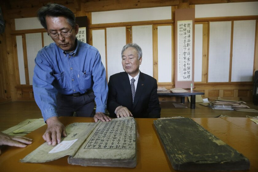 In this Oct. 13, 2015 photo, Hwang You Yeon, left, points at his family's two-volume gemological book written in 1723 at a museum commemorating one of his prominent ancestors in Paju, South Korea. Historic clan villages keep centuries-old genealogical books that they say have been handed down from generation to generation. The Yun family in Paju keeps woodblocks used to publish its family tree from 1630 to 1863; and Kim Sun Won has a modern version of genealogical books at his home. (AP Photo/Ahn Young-joon)
