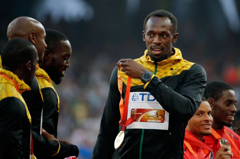 Jamaica's Usain Bolt holds his gold medal to teammates Nickel Ashmeade, Asafa Powell and Nesta Carter on the podium during the ceremony for the men's 4x100m relay final at the World Athletics Championships at the Bird's Nest stadium in Beijing, Sunday, Aug. 30, 2015. (AP Photo/Ng Han Guan)
