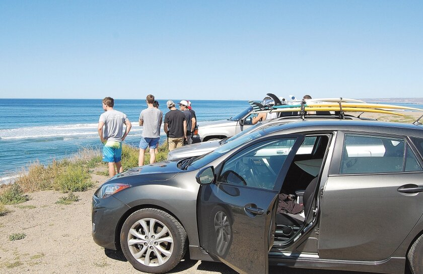 A group of surfers surveys the ocean waves from the top of a bluff at K-38 along Mexico's Highway 1. The surfing spot is just a few minutes north of the Las Gaviotas compound in Baja California.