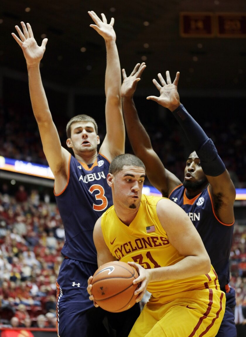 Iowa State forward Georges Niang, center, looks to pass in front of Auburn defenders Benas Griciunas, left, and KT Harrell, right, during the first half of an NCAA college basketball game Monday, Dec. 2, 2013, in Ames, Iowa. (AP Photo/Charlie Neibergall)