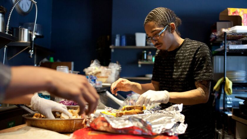 Employee Keenan Leal, 23, prepares food at the Manifesto Cafe in Los Angeles on April 9, 2015.