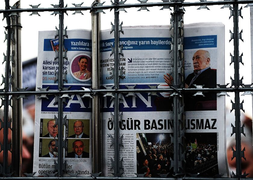 A supporter holds a copy of the Turkish newspaper Zaman behind a fence as police arrest its editor in chief in Istanbul on Sunday.