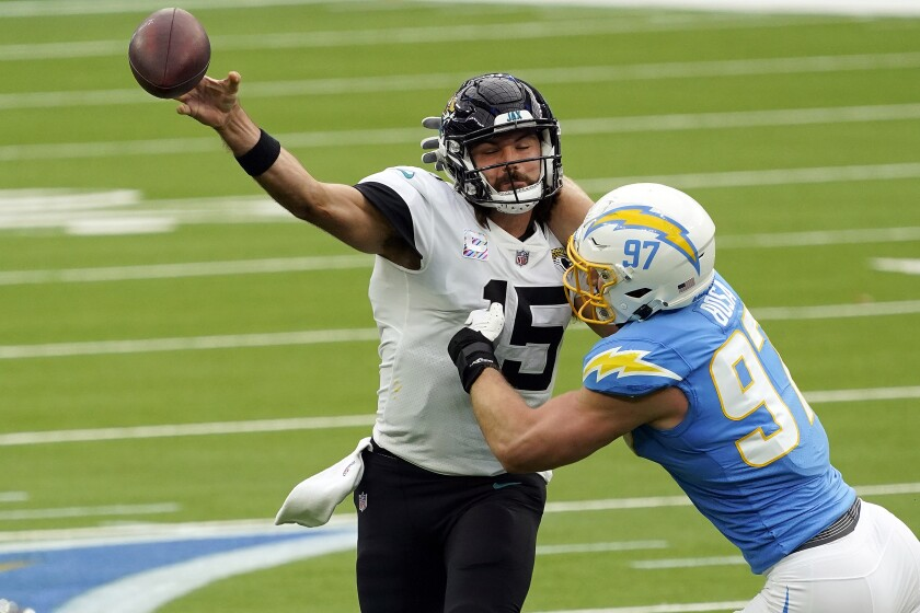 Jacksonville Jaguars quarterback Gardner Minshew, left, throws under pressure from Los Angeles Chargers defensive end Joey Bosa during the first half of an NFL football game Sunday, Oct. 25, 2020, in Inglewood, Calif. (AP Photo/Alex Gallardo )