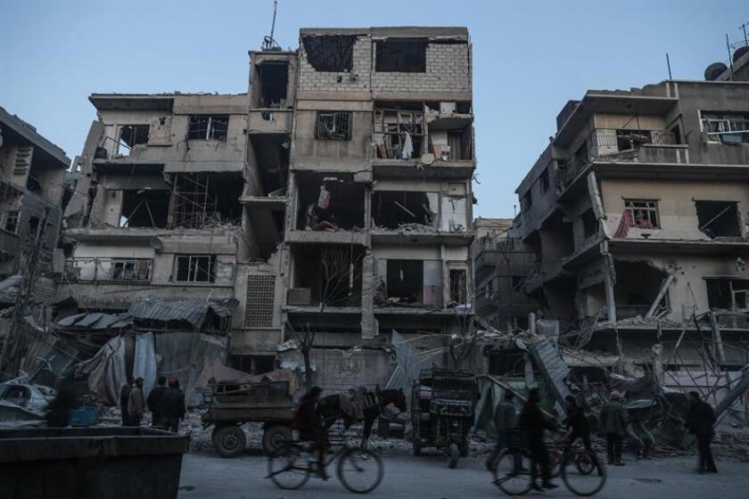 Fotografía que muestra a varias personas mientras inspeccionan un edificio civil dañado por bombardeos en Duma, Guta Oriental (Siria). EFE/Archivo
