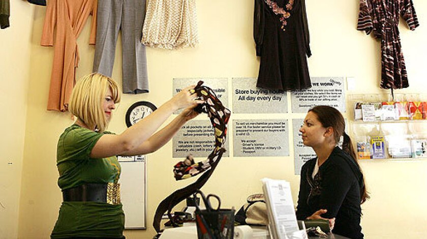 Crossroads Trading Co. manager Christie Cook, left, evaluates an item offered for resale by Amber Sheikh.