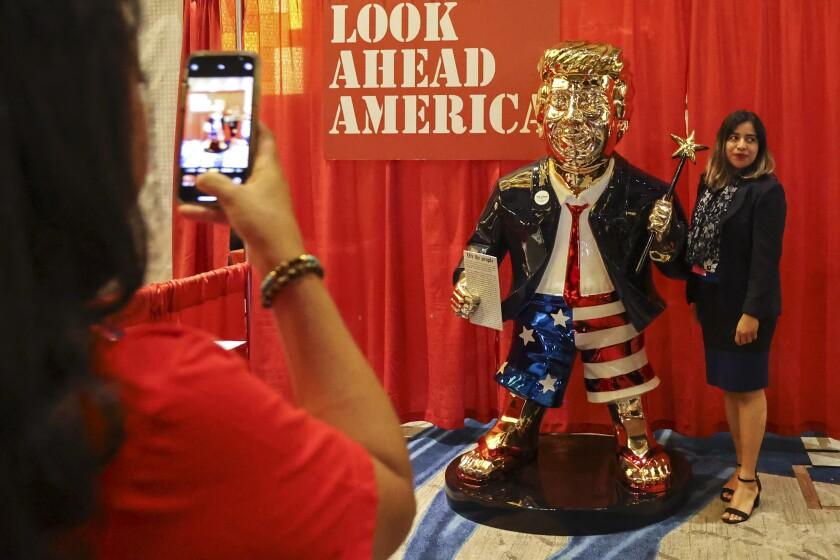 Una mujer se toma una foto junto a una estatua dorada de Donald Trump