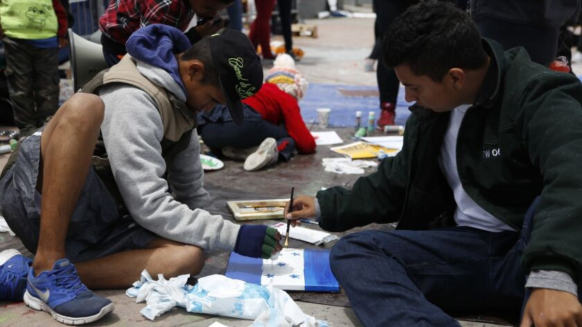 Alejandro (left) from El Salvador and Jose (right) from Honduras paint an Honduras flag. Activate Labs a non-profit organization brought art supplies to the Chaparral border.