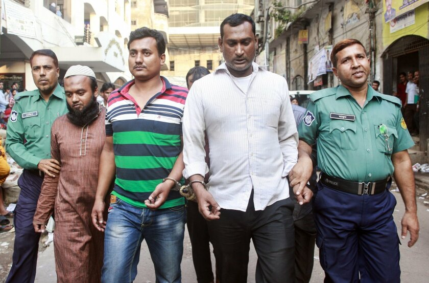 Bangladeshi police escort men detained in the suspected murder of 60-year-old Hiroe Miyata, a Japanese businesswoman, outside a court in Dhaka, Bangladesh, Tuesday, Nov. 24, 2015. Police in Bangladesh have opened a murder investigation in the disappearance of the Japanese businesswoman following reports that her body was buried in a graveyard under a false name. On Tuesday, a Dhaka court gave police four days to interrogate five people detained in connection with the case, a police official said on condition of anonymity because higher authorities had asked police not to talk to the media in detail about the case for now. (AP Photo/Suvra Kanti Das)