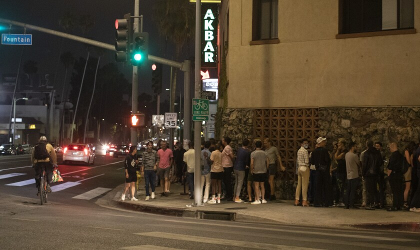 A line of people outside a bar.