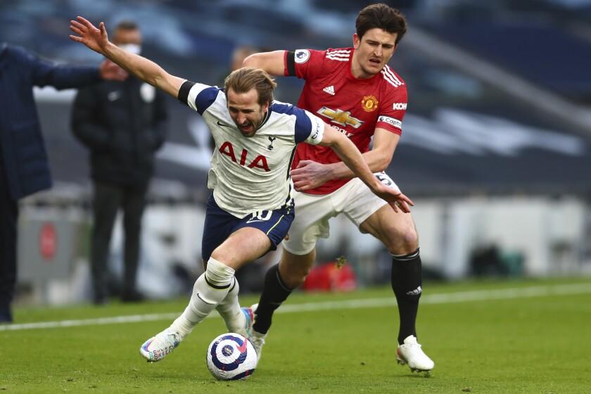 Harry Kane (izquierda) de Tottenham pugna el balón con Harry Maguire del Manchester United