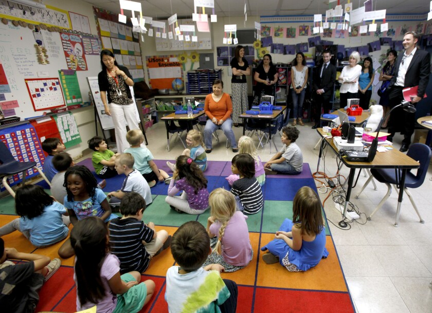 French dignitaries, including Senator Claudine LePage, visited the French immersion Kindergarten class, taught by Valerie Sun, standing next to children, at Franklin Magnet Elementary School in Glendale in May 2013.