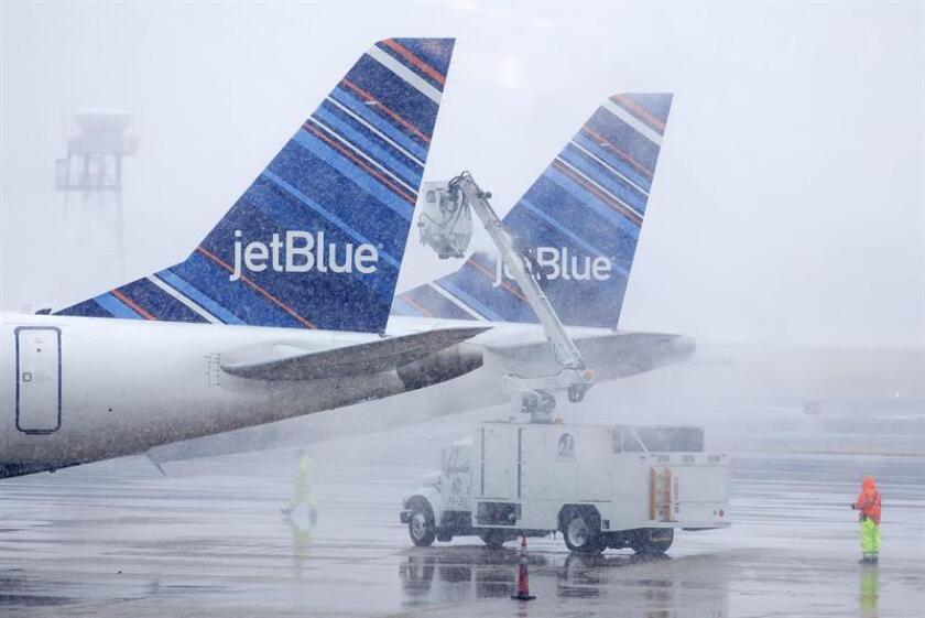 Unos operarios deshielan el fuselaje de unos aviones de la aerolínea JetBlue durante una tormenta de nieve en el aeropuerto Ronald Reagan - Washington en Arlington, Virginia, Estados Unidos. EFE/Archivo