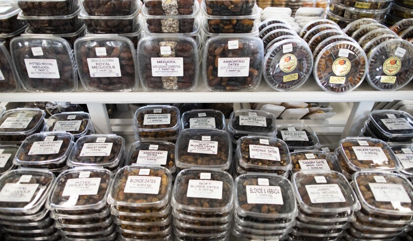 Clear containers filled with dates line two shelves.