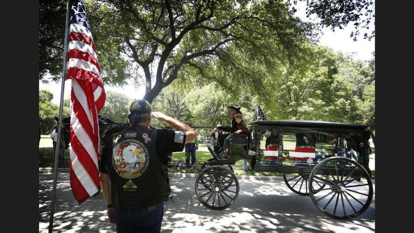 Magnus, the 8-year-old son of slain Dallas Police Officer Lorne Ahrens, rides with his father's coffin during the funeral Wednesday afternoon. Sr. Cpl. Ahrens and four other officers were killed in an attack during a Black Lives Matter protest on July 7.
