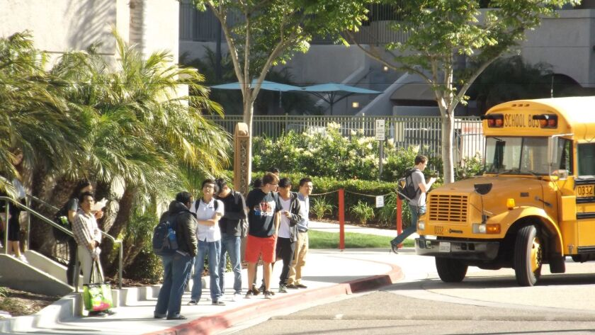 Students wait for the school bus May 2 near the pool area where a mass shooting took place, April 30