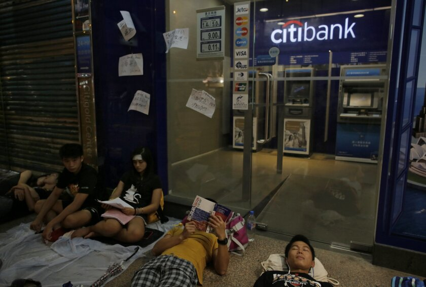 Protesters rest outside a shopping mall during a rally in Hong Kong, Thursday, Oct. 2, 2014. Shops in Hong Kong have closed and the local stock market has plunged but protesters are gambling their agitation for greater democracy will pay off by preserving institutions that made this former British colony a profitable asset to China. (AP Photo/Vincent Yu)