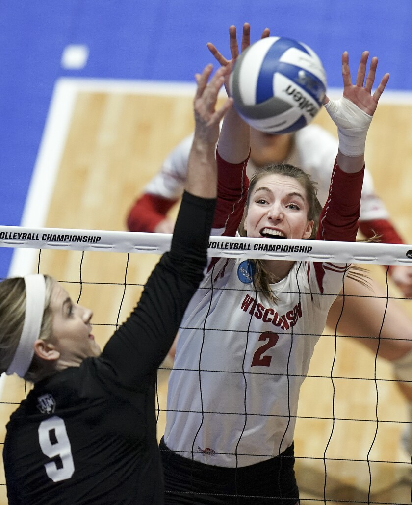 In this Dec. 13, 2019, photo, Wisconsin's Sydney Hilley (2) tries to block the shot of Texas A&M's Hollann Hans (9) during an NCAA volleyball match at the UW Field House in Madison, Wisc. Wisconsin's football team continues practicing amid a pandemic knowing the start of its season is only a week away. Members of the Badgers' other fall sports teams must take a more patient approach. (Steve Apps/Wisconsin State Journal via AP)