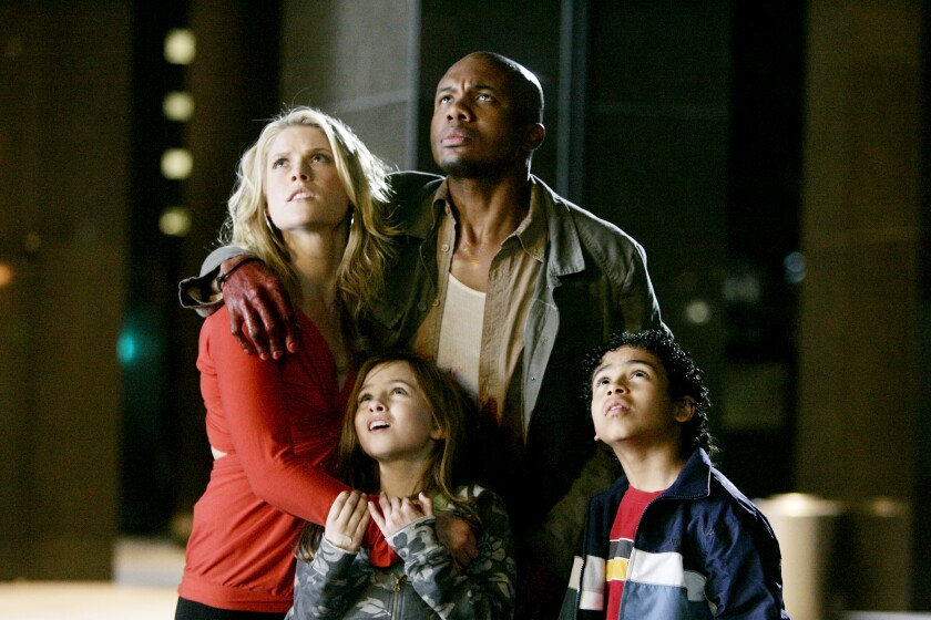 """Ali Larter and Leonard Roberts in a scene from """"Heroes,"""" with two child actors"""