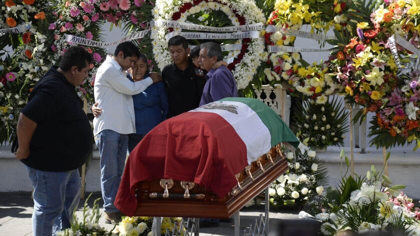 Family members of the slain mayor of Temixco, Gisela Mota, mourn next to her casket, during a ceremo