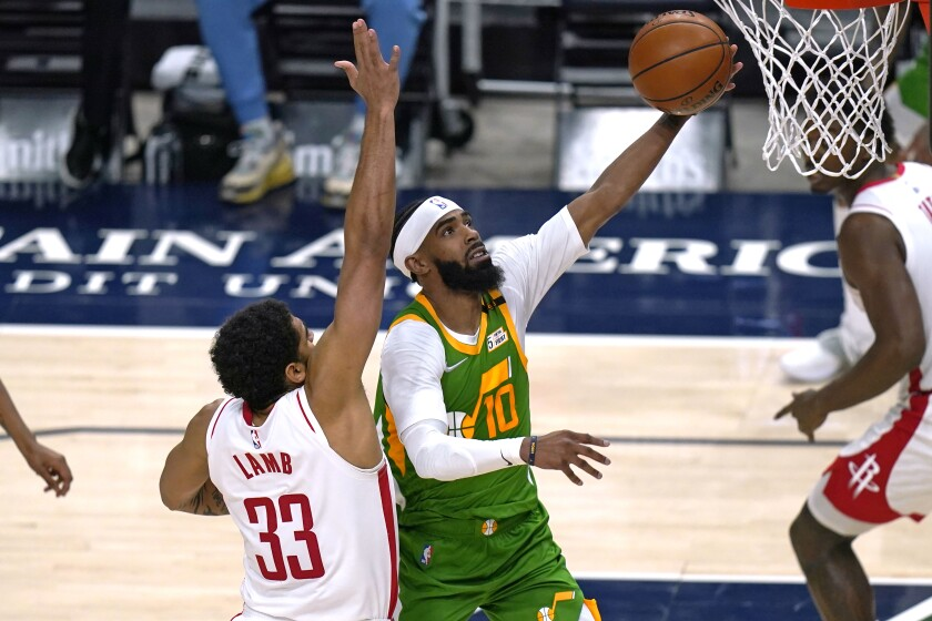 Utah Jazz guard Mike Conley (10) lays the ball up as Houston Rockets Anthony Lamb (33) defends defends during the second half of an NBA basketball game Friday, March 12, 2021, in Salt Lake City. (AP Photo/Rick Bowmer)