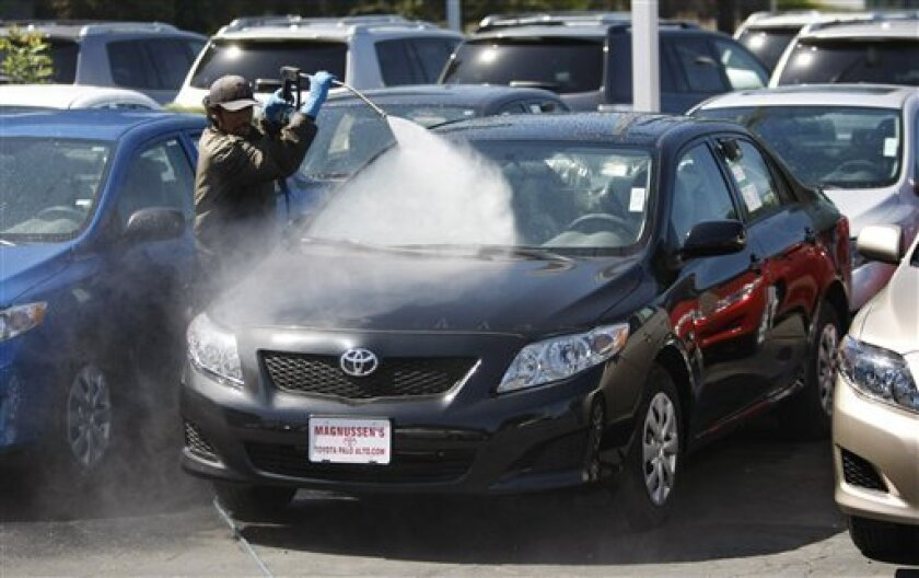 FILE - In this Sept. 23, 2010 file photo, a worker washes a Toyota 2010 Corolla at a Toyota dealership in Palo Alto, Calif. It would be easy to think Toyota's biggest problem is its damaged reputation caused by sudden acceleration recalls, millions in government fines and massive lawsuits and settlements. But what's hurting the company most is an aging lineup of boring cars.(AP Photo/Paul Sakuma, file)