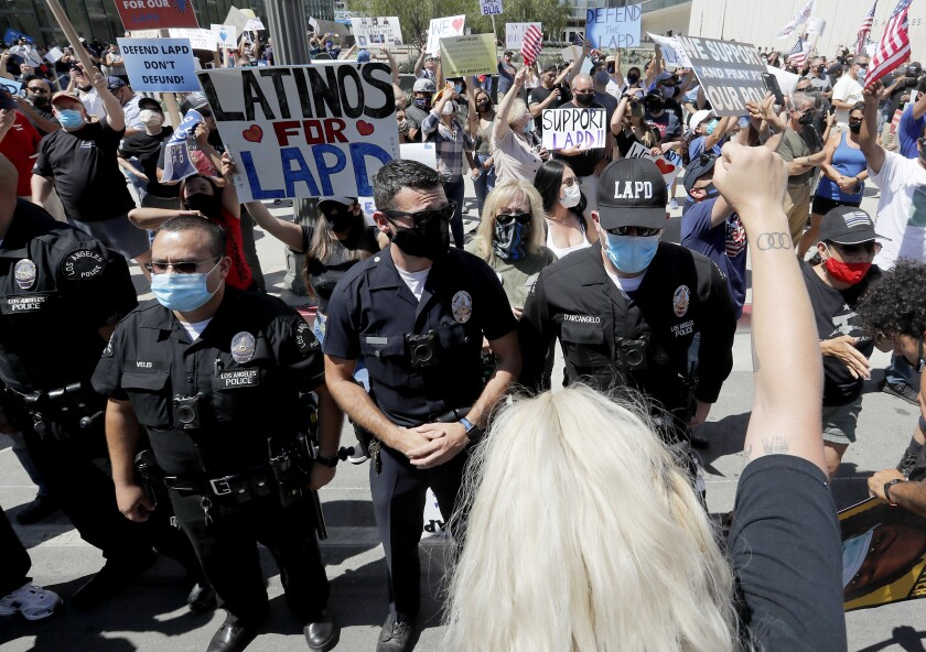 LAPD officers form a line to separate pro- and anti-police demonstrators outside LAPD headquarters in downtown Los Angeles