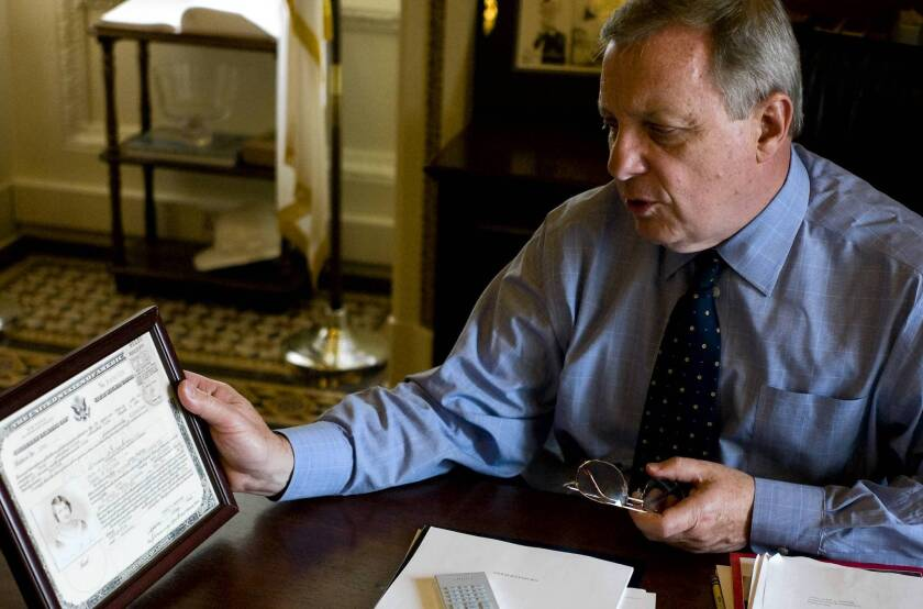 Sen. Richard J. Durbin (D-Ill.) with a framed copy of his mother's naturalization certificate.