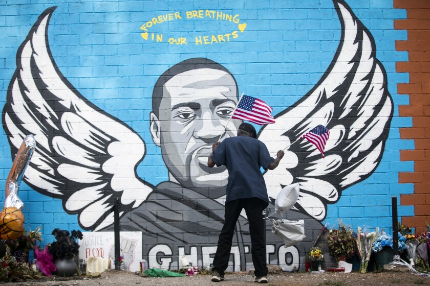 A man places two flags at the foot of the mural honoring George Floyd in Houston.