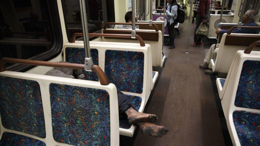 The feet of a homeless man hang over seats as he sleeps inside a Metro Red Line subway car inside Un